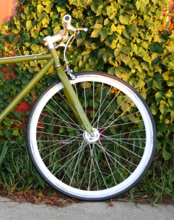Green single-speed against ivy-covered wall